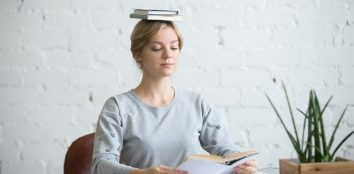 A young woman balancing books on top of her head