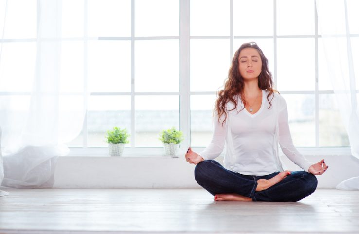 A young woman meditating in her home