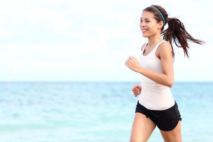 A young woman running along the beach