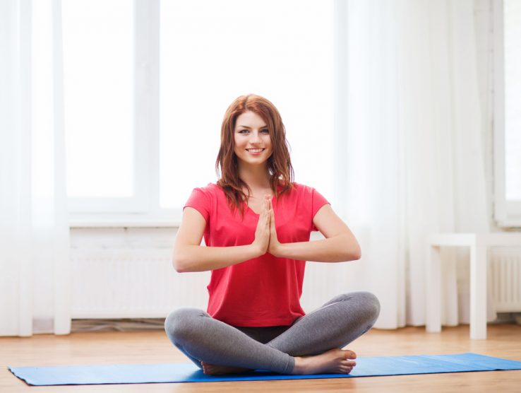 A young woman sitting up in a yoga pose