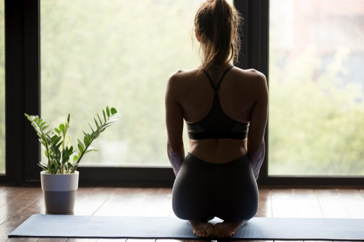 A young women in her house doing a sat up yoga pose