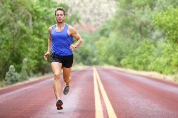 An athletic man running down the road