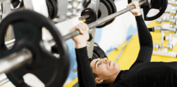 An average build man bench pressing in the gym