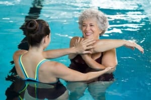 An elder lady stretching before she does aqua therapy