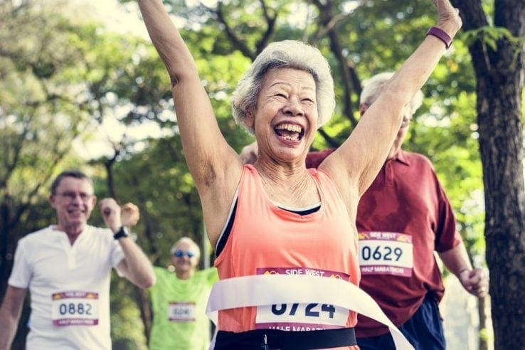An elderly lady smiling as she crosses the line in a half marathon