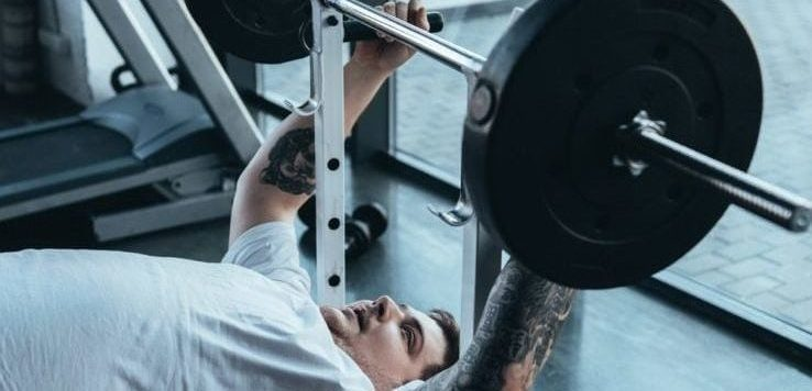 An overweight man bench pressing in the gym