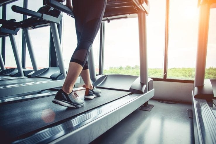 Close up of a woman while she walks on a treadmill