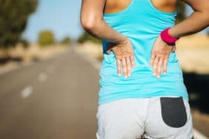 Female runner having problems with the middle of her back