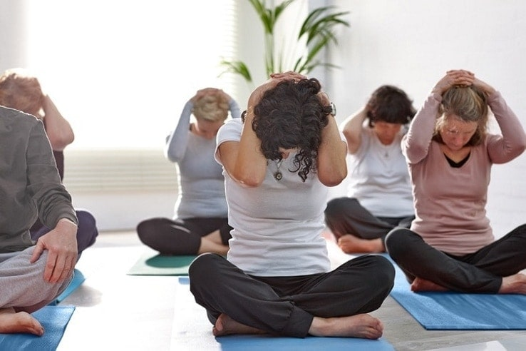 Group of people exercising their necks during yoga class