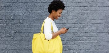 Happy young woman reading text message on mobile phone