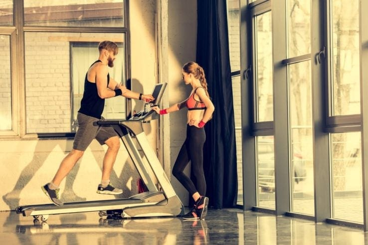 Man doing hit training on a treadmill while a woman watches
