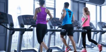 Multiple people running on treadmills side by side
