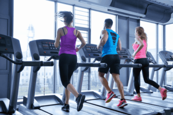 Multiple people running on treadmills side by side