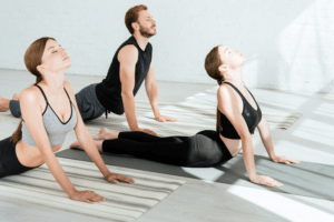 Three people doing the same yoga pose together to stretch their backs