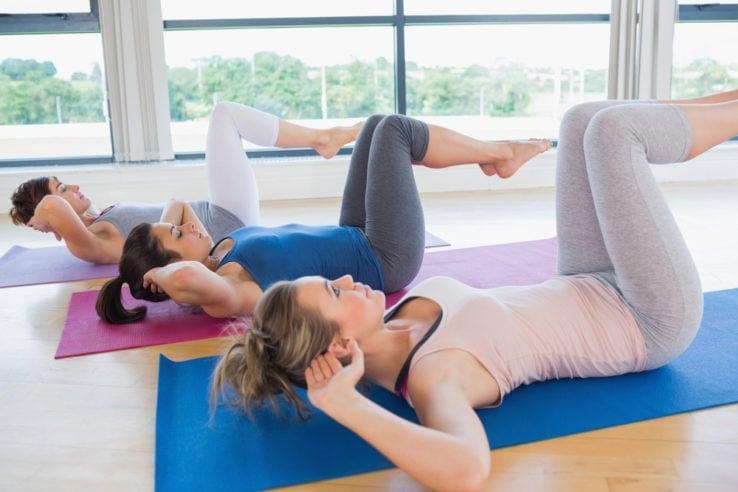 Three women doing core exercises on yoga mats