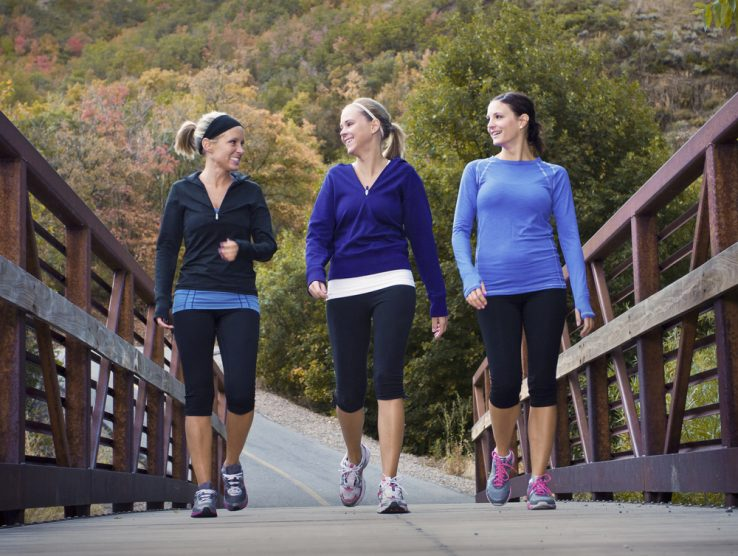 Three women walking over a bridge toegther