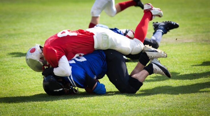 Two american football players tackling each other
