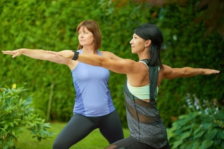 Two mature women keeping fit by doing yoga in the garden