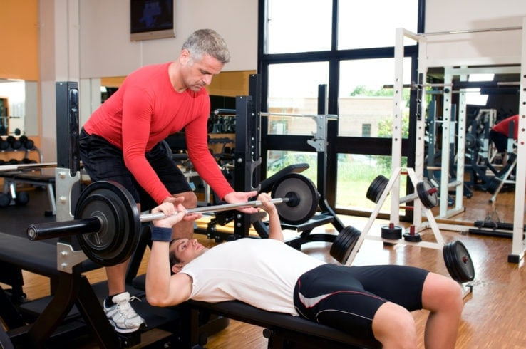 Two men benchpressing together in the gym