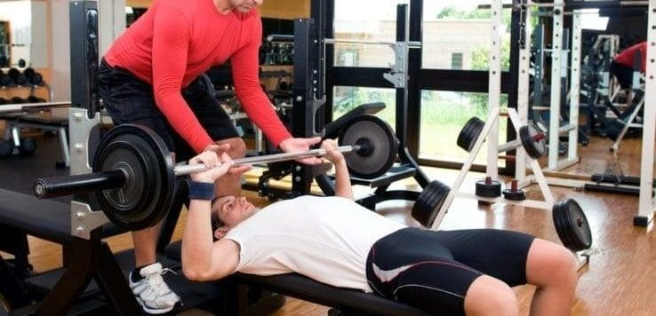 Two men bench pressing together in the gym