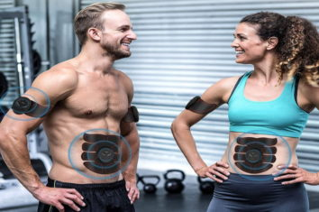 a couple using ab stimulators while training in the gym