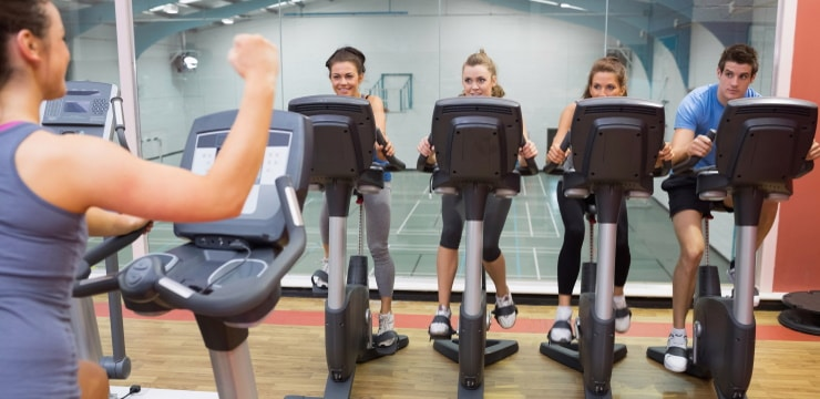 a group of people exercising together using exercise bikes in the gym