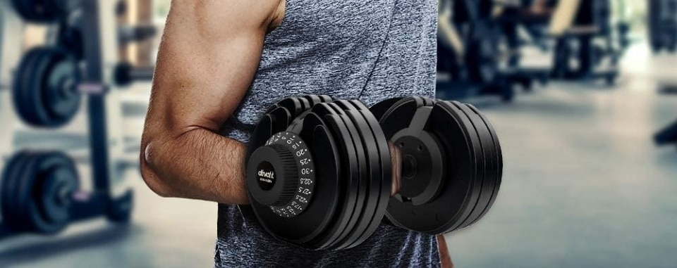 a guy using an adjustable dumbbell in the gym