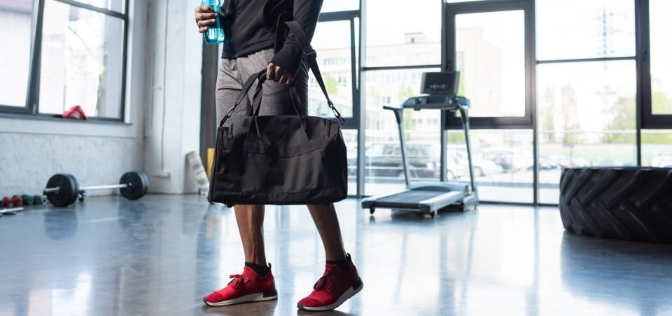 a man carrying a gym bag by the hand