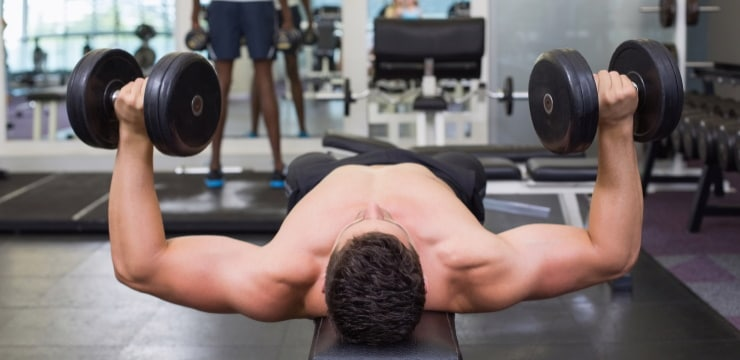 a man doing chest press, with dumbbells