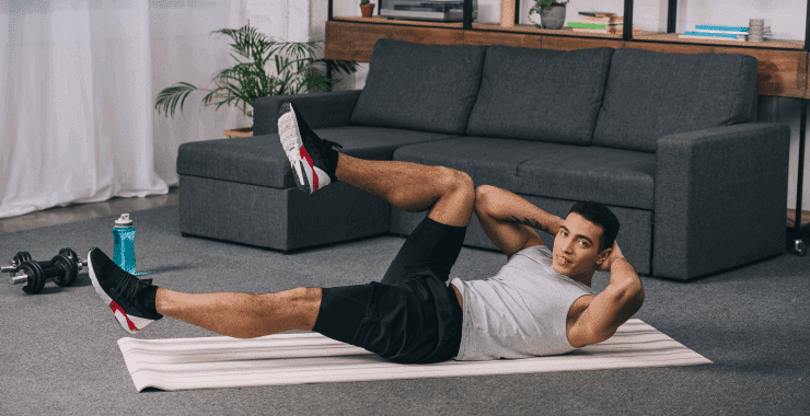 a man doing sit-ups on the floor of his living room