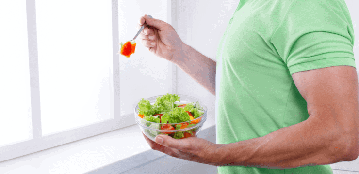 a man eating a salad near a window