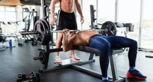 a man exercising in the gym with a bench press