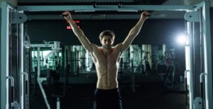 a man exercising in the gym with pull ups