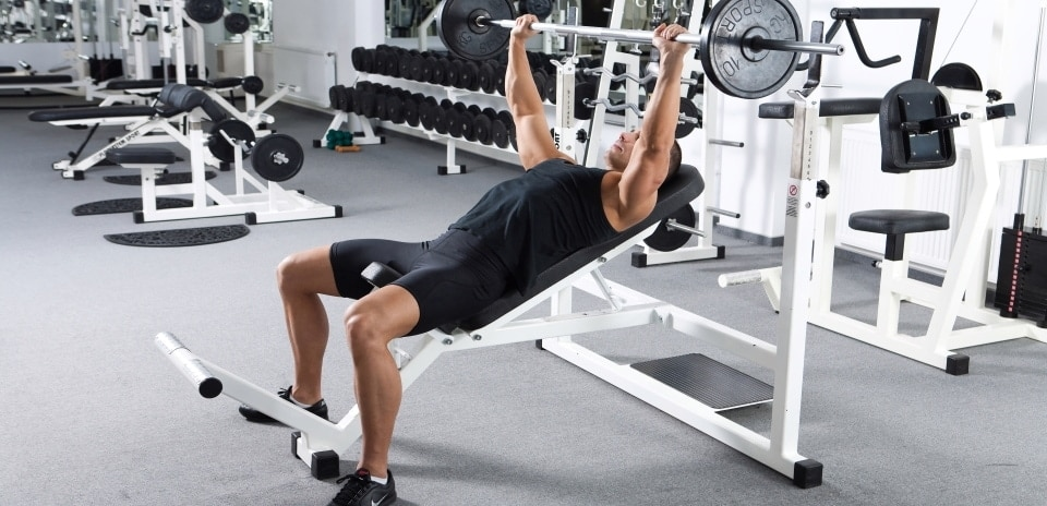 a man exercising on an olympic weight bench