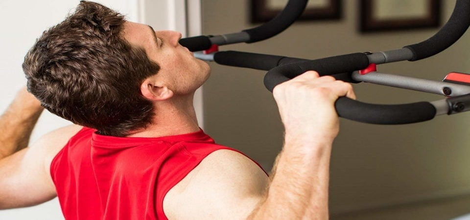 a man exercising on pull-up bar in home