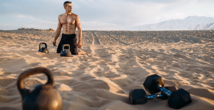 a man exercising on the beach with dumbbells and kettlebells
