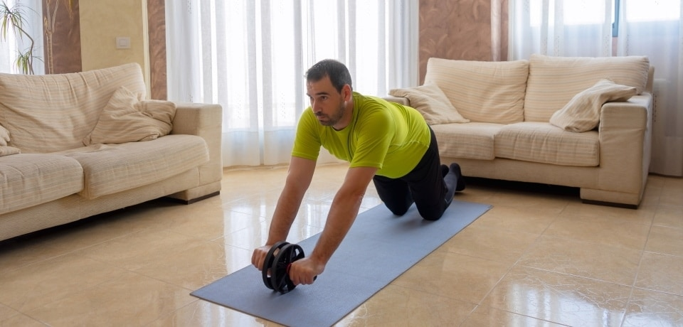 a man exercising with an ab roller in the living room