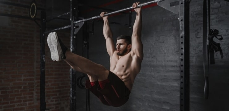 a man hanging on the bar with his legs raised
