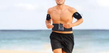 a man using an ab toning belt while he runs on the beach