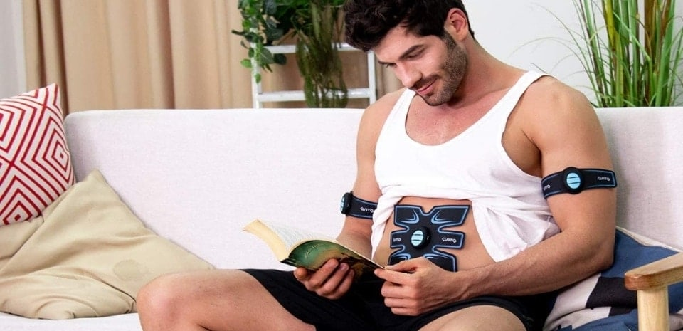 a man reading a book while using an ab stimulator