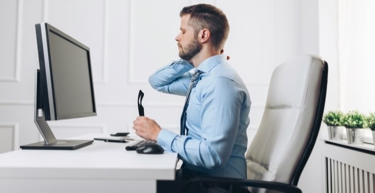 a man sitting in a chair rubbing his neck because of his bad posture