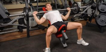a man training in the gym with olympic weight bench