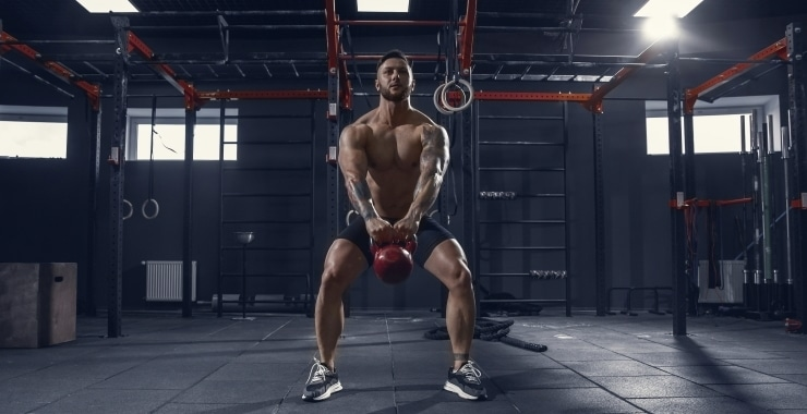a man training with a kettlebell in the gym