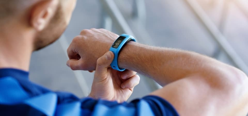 a man watching his blue fitness tracker