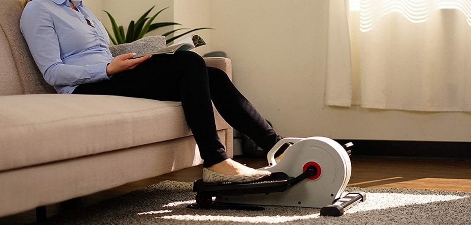 a person exercising with an elliptical while reading