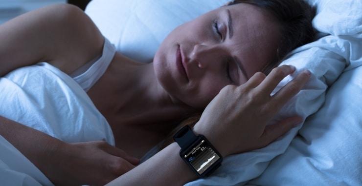 a woman sleeping wearing a fitness tracker