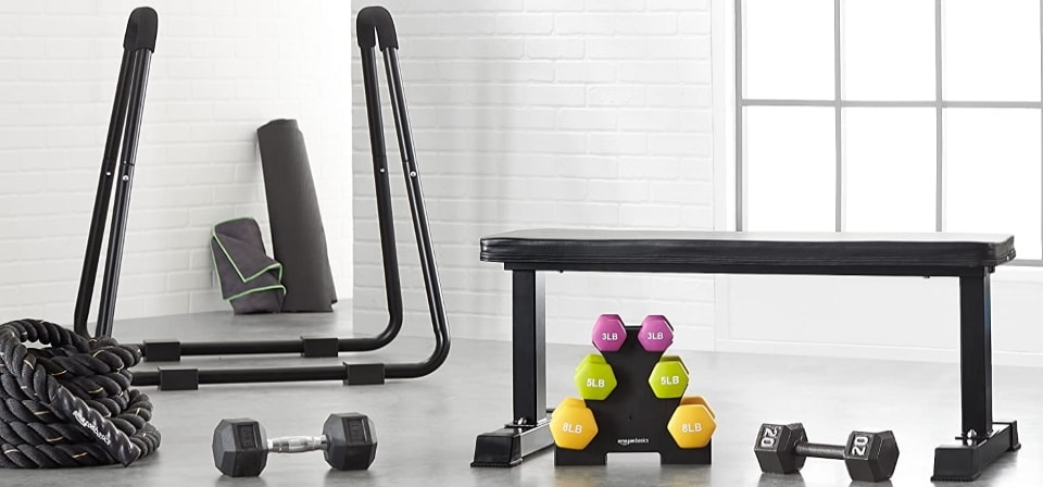 a weight bench next to a dumbbell set