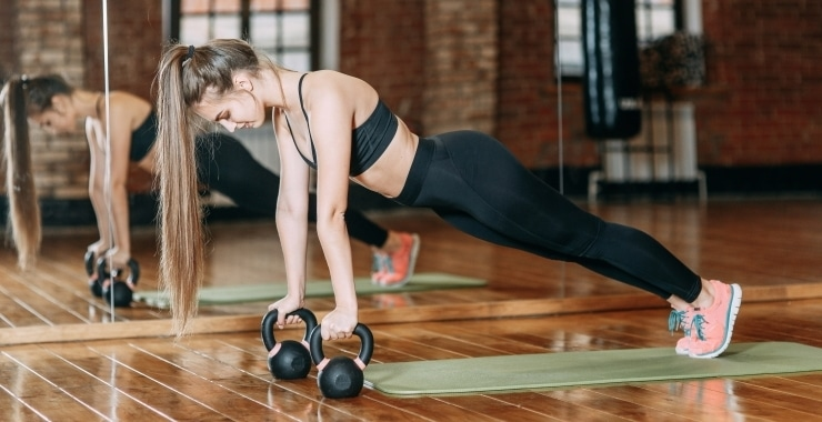 a woman doing push-ups with kettlebells