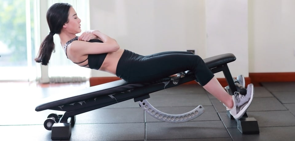 a woman doing sit-ups on a bench