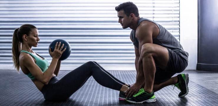 a woman doing sit-ups with a personal trainer